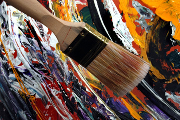 Large painting brush over abstract colored background