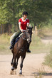 Girl in red t-shirt on riding horse