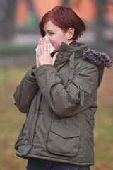Girl blowing her nose outdoors in late autumn.