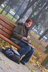 Lonely girl with a laptop siting on a bench in an autumn park.