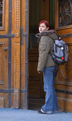 Young redheaded student opening the university doors.