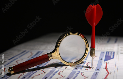 A magnifying glass and a dart on stockmarket news