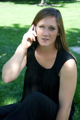 Beautiful Girl in a Black Dress Talking on a Cell Phone