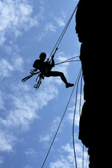a man-climber rises on the wall with the help of the ropes