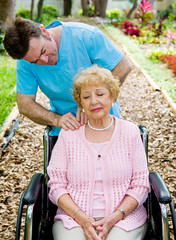 Senior woman in wheelchair receives massage therapy