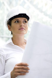 Woman in hardhat, holding blueprints poster