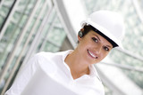 Woman wearing a hardhat holding plans poster