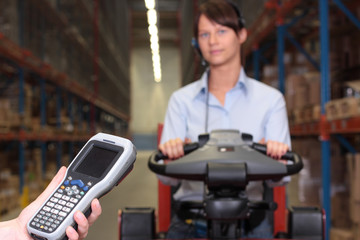 bar code reader -woman worker on forklift in background