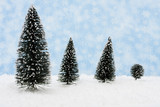 Four evergreen trees on snow with snowflake background poster