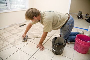 Installer filling ceramic tile with grout,