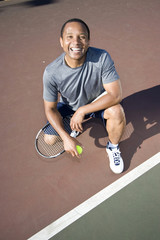 Smiling tennis player kneeling down on court. Vertical