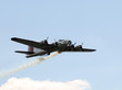 World War II era Flying Fortress bomber with smoke trail