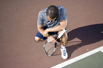 Tennis player crouched down in defeat.  Horizontal