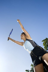 Tennis player jumping with hands in air. Vertical