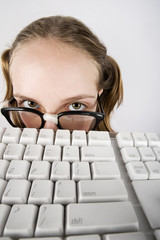 Nerdy Young Girl Peeking Over a Computer Keyboard