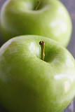Two green granny smith apples, with focus on front apple stem. poster