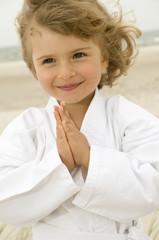 Little girl exercising in the beach