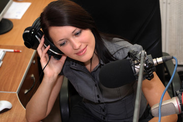 A radio DJ is listening to radio broadcasting
