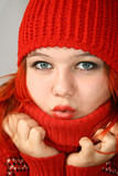 Young girl hides into the collar of the red sweater poster