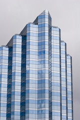 A modern blue and grey glass building on a grey background