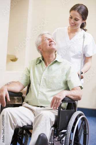 Nurse Pushing Man In Wheelchair
