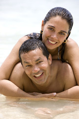 Beautiful couple in love at the beach hugging each other