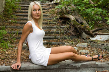 Pretty blond girl is sitting on the old stairs in the park