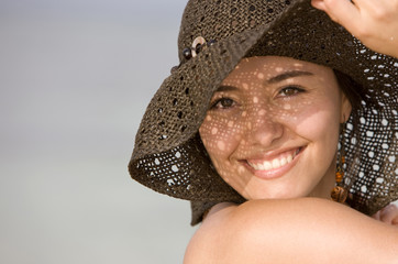 Beautiful beach girl portrait - smiling with hat