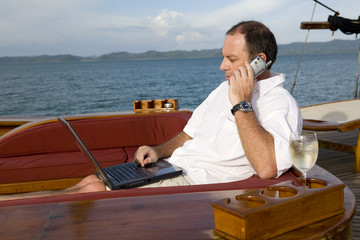 man on deck of yacht with mobile phone and laptop