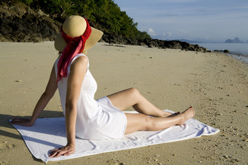 Woman with dress and sun hat relaxing on the beach