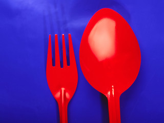 Brightly red spoon and plug on  dark blue background
