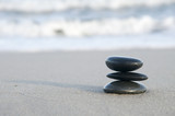 Black smooth pebbles  on a sandy beach. poster