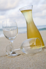 Carafe of white wine and glasses on beach