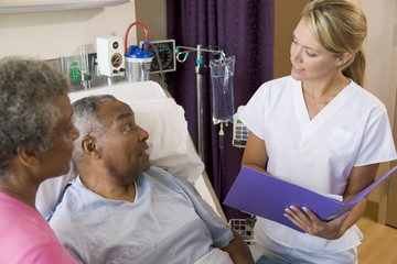 Doctor Talking To Senior Couples,Making Notes