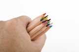 The hand grasps the color pencils on a white background poster