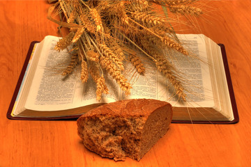 wheat, bread and Holy Bible on table
