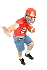 Middle aged man in his high school football jersey & helmet