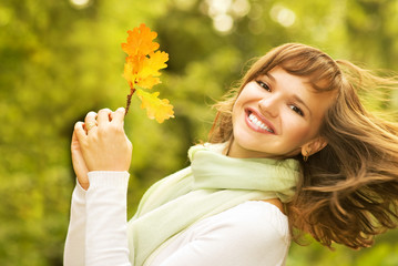 Beautiful romantic brunette with golden autumn leaf