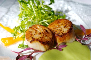 An image of gourmet seared scallops with garnishes