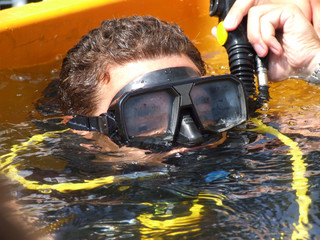 The rescuer-diver shows immersing in water