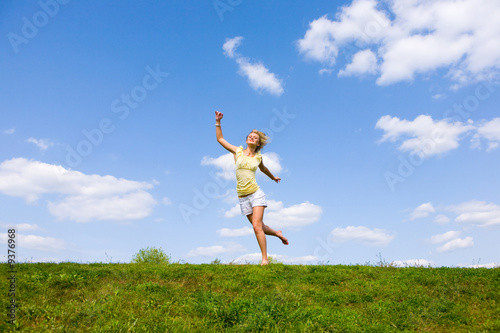 Happy young woman is running in a field