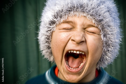 Close-up of portrait of crazy kid screaming loudly
