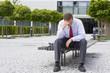 Frustrierter Geschäftsmann sitzt auf Bank vor Bürogebäude