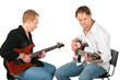 Two sitting men play on guitars