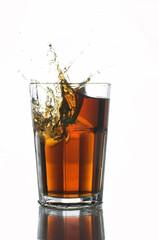 Eiswürfel fällt in ein Glas Cola