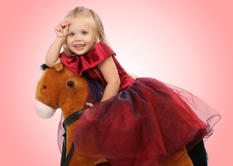Portrait of the beautiful girl on a toy horse