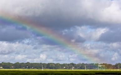 rainbow over coastal marsh with boats