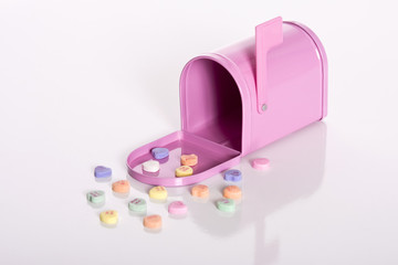 Pink mailbox surrounded by valentine candy hearts