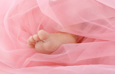 Part of a leg of the newborn girl under a pink coverlet