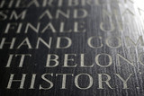 A closeup of the word HISTORY engraved on a war memorial. poster